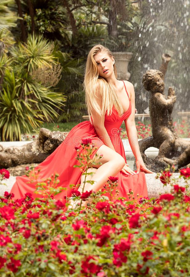 Fashion blonde woman in red maxi dress posing in garden. stock photography