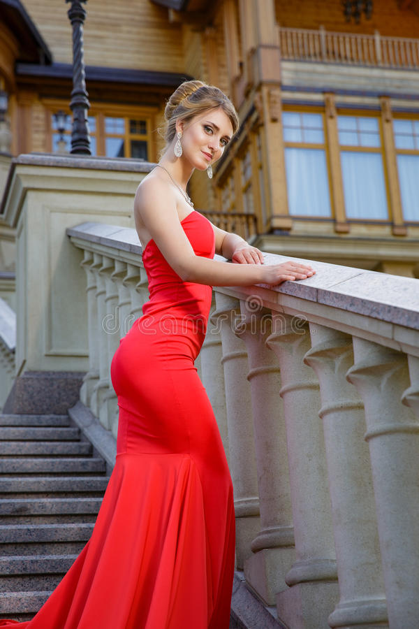 Fashion outdoor photo of beautiful woman in luxurious red dress posing on stairs in villa stock photography