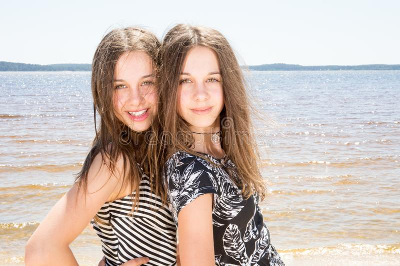 Outdoor photo of two beautiful young girls Beauty portrait of twins sisters royalty free stock photos