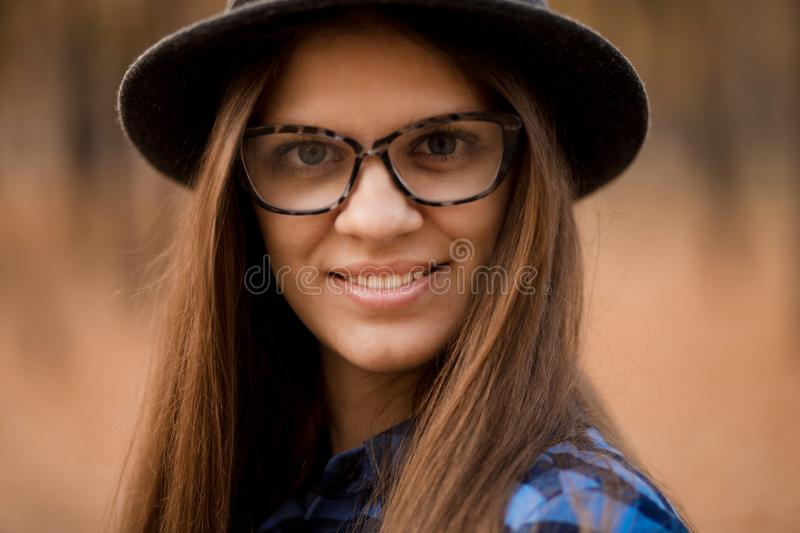 Fashion outdoor portrait of young woman with hat and glasses in fall, retro style color tones. stock photography