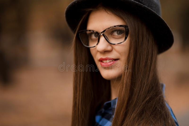 Fashion outdoor portrait of young woman with hat and glasses in fall, retro style color tones. royalty free stock photos