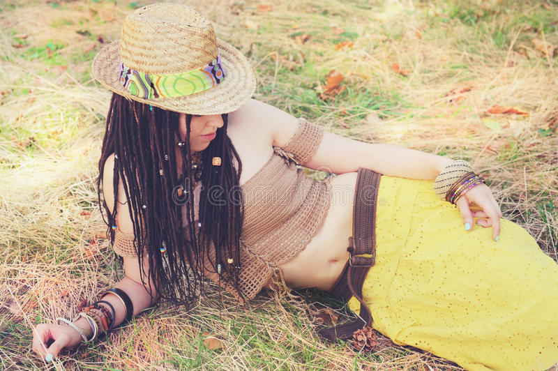 Fashion outdoor woman portrait with dreadlocks, dressed in knitted top, yellow skirt and straw hat, resting on the dry grass in pa royalty free stock photography