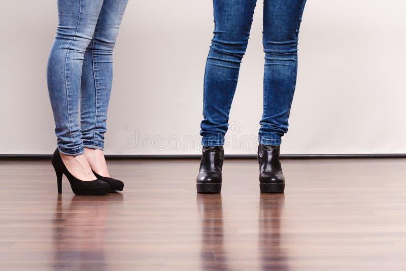 Female legs in denim pants heeled shoes. Fashion outfit. Female legs in denim pants and black high heels shoes royalty free stock image