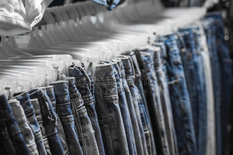 Fashion pants and jeans on the rack in clothing store. Sale, shopping, fashion, style concept. Jean Pants Hang on Shelf stock photos