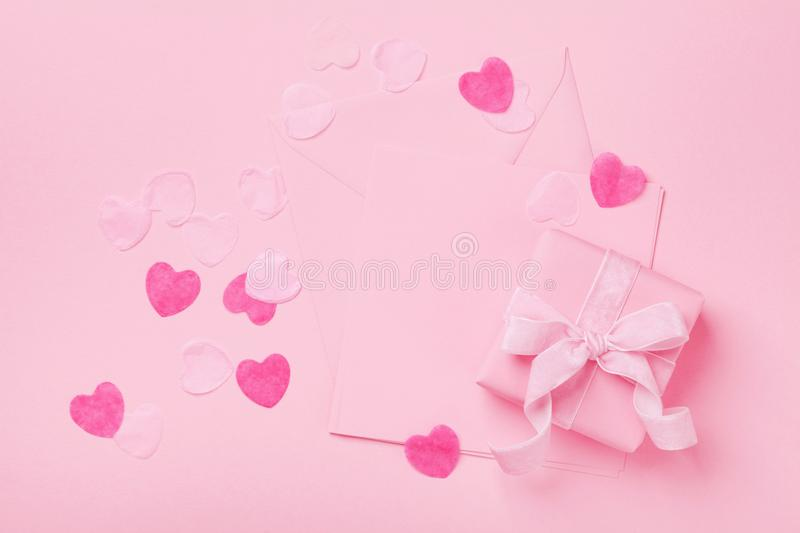 Fashion pastel mockup. Gift or present box and envelope on pink table top view. Greeting card for Valentines, Woman or Mothers Day royalty free stock images
