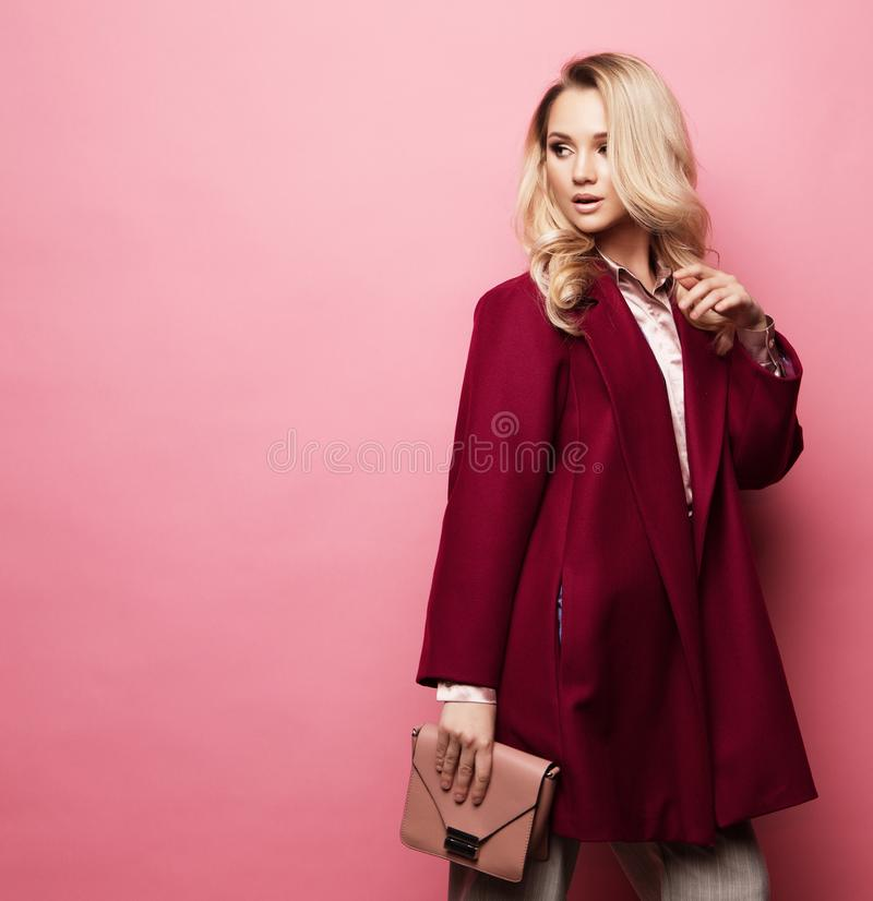 Fashion, people and lifestyle concept: Beautiful woman long blond curly hair wear cashmere coat and holding handbag. royalty free stock images