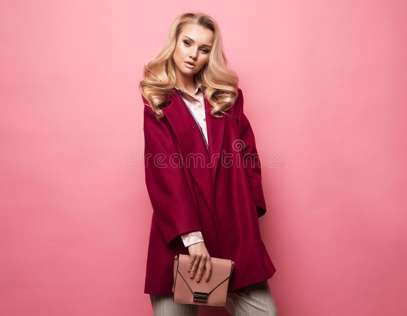 Fashion, people and lifestyle concept: Beautiful woman long blond curly hair wear cashmere coat and holding handbag. royalty free stock photography