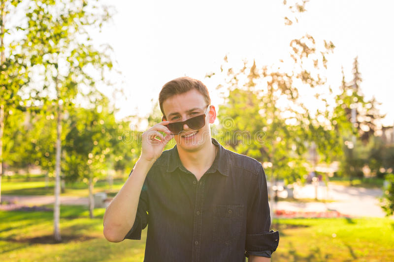 Fashion, people and lifestyle concept - Close-up portrait of happy cheerful confident handsome man in sunglasses in park royalty free stock photography