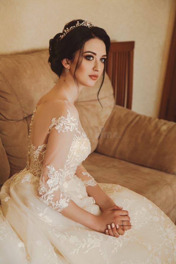 Beautiful bride in elegant wedding dress and diadem posing in r stock photography