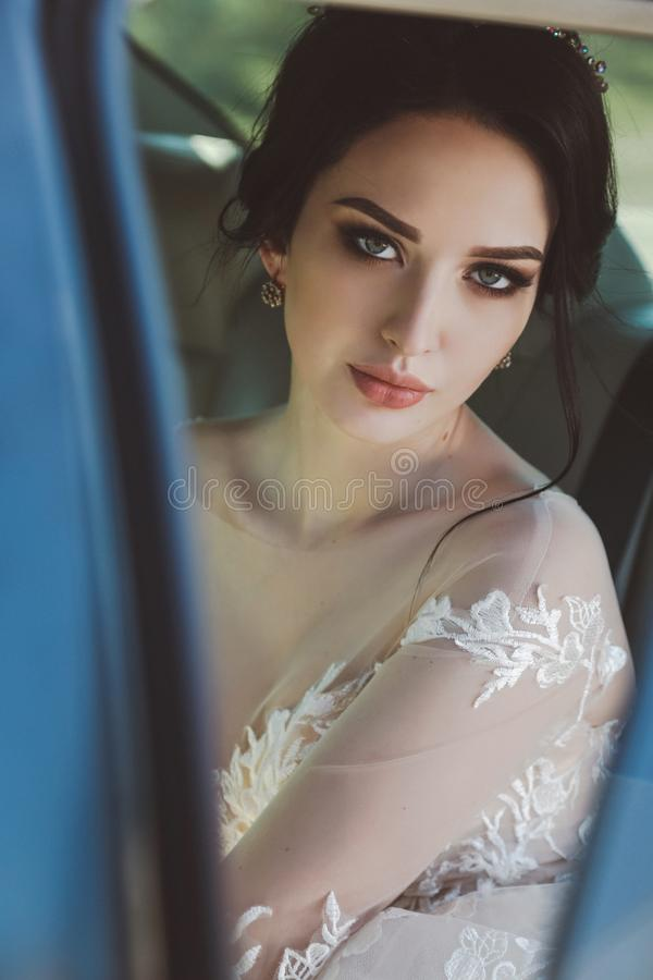 Beautiful bride with dark hair in elegant wedding dress, posing stock photography