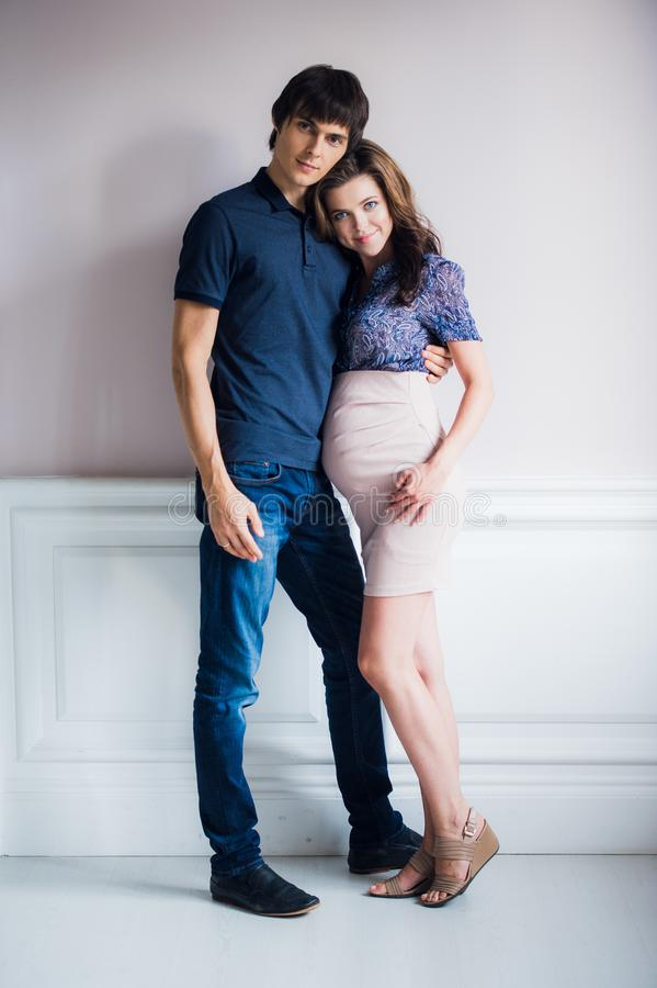 Fashion photo of beautiful couple in elegant clothes. handsome young man posing with gorgeous pregnant wife stock image