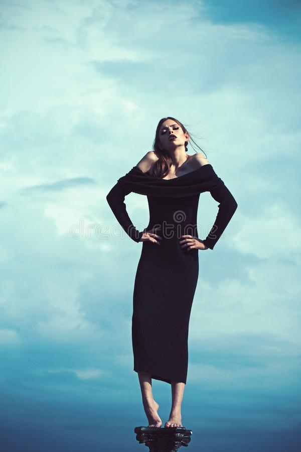 Fashion photo of a beautiful elegant young woman in a pretty black dress posing over blue sky background. Fashion photo stock photography