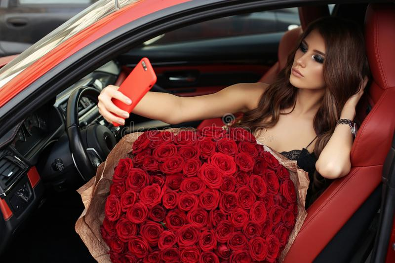 Beautiful girl in elegant dress posing in luxurious car with bo. Fashion photo of beautiful girl with dark hair in elegant dress posing in luxurious car with royalty free stock photos