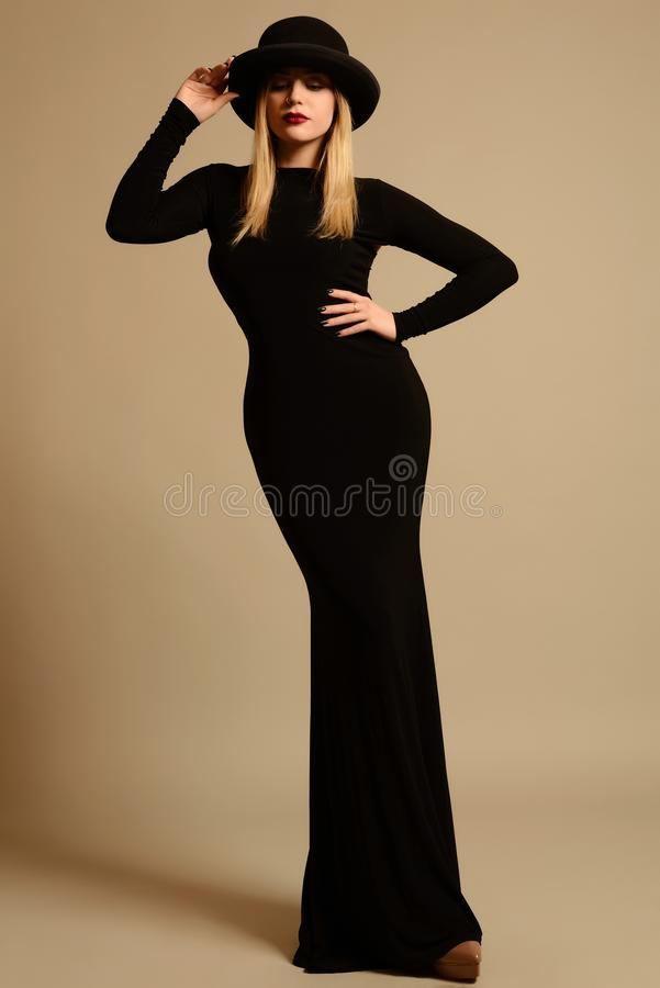 Fashion photo of beautiful lady in elegant black dress and hat royalty free stock image