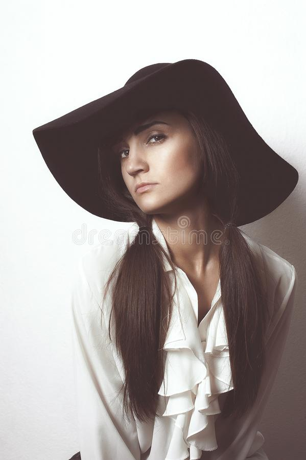 Fashion photo of beautiful lady in elegant black hat and white s royalty free stock photos