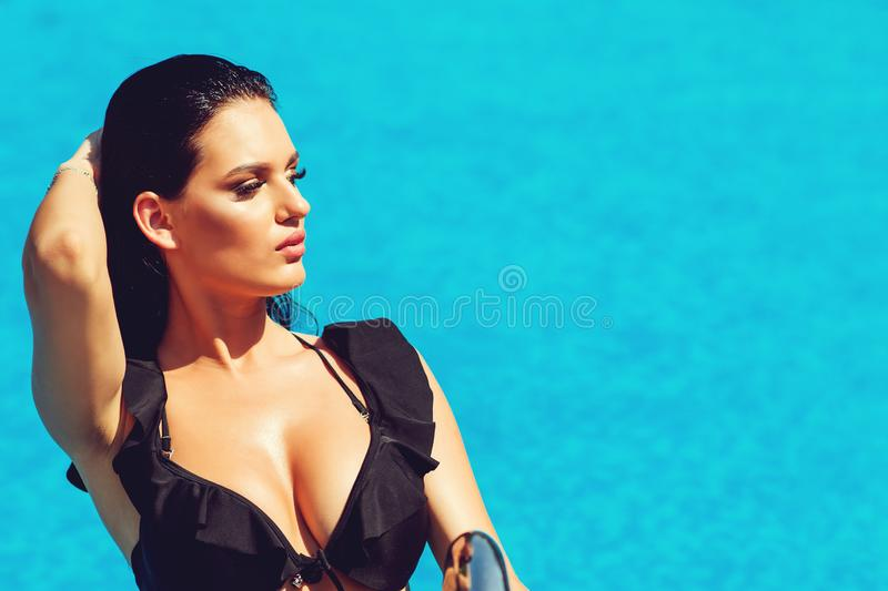 Fashion photo of beautiful sexy woman with brunette wet hair in luxurious swimming suit relaxing in swimming pool. Fashion and royalty free stock photo