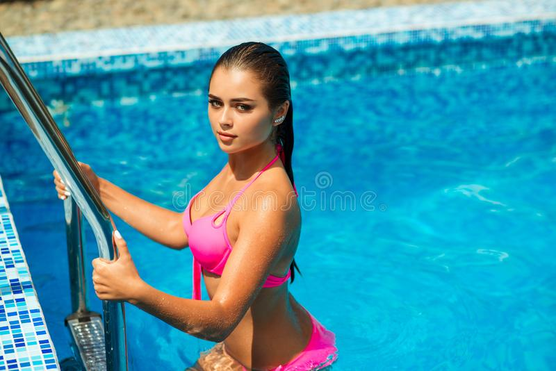 Fashion photo of beautiful sexy woman with perfect tanned body, wet hair and amazing eyes. Girl wears elegant pink bikini. stock photo