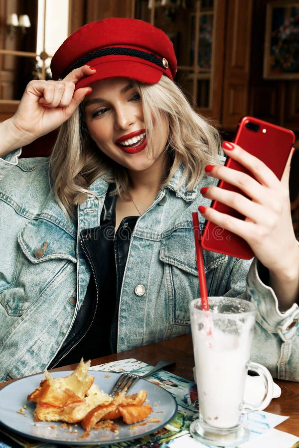 Beautiful woman with blond hair in casual clothes and red hat sitting in cafe. Fashion photo of beautiful woman with blond hair in casual clothes and red hat stock image