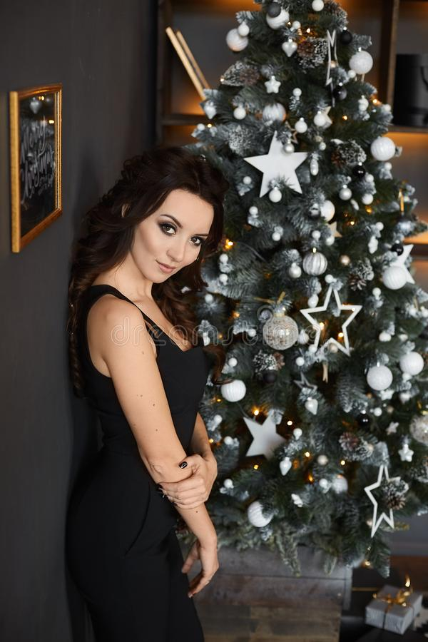 Fashion photo of beautiful woman with dark hair in elegant black suit with Christmas tree on background. Sexy brunette royalty free stock photo