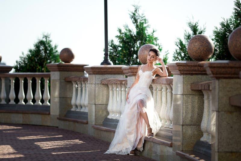 Fashion photo of beautiful woman in wedding dress posing outdoor. Fashion photo of beautiful woman in wedding dress posing outdoor royalty free stock image