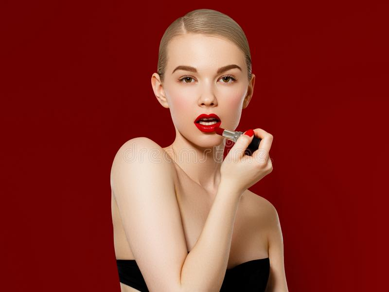 Fashion photo. Closeup of woman face with bright red matte lipstick on full lips. Beauty Cosmetics, Makeup Concept. A royalty free stock image