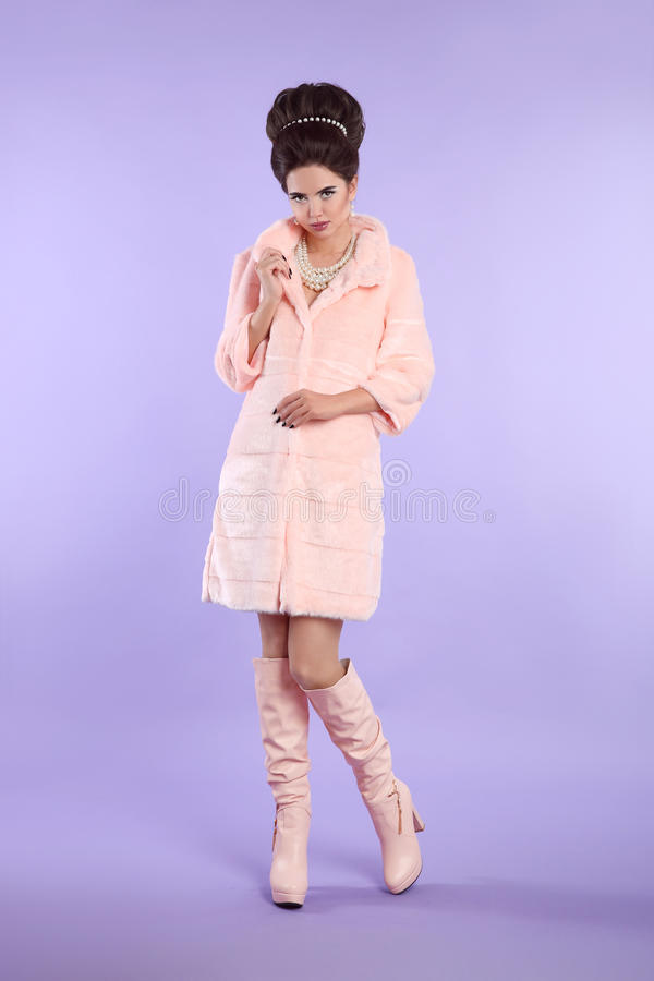 Fashion photo of fashionable model in pink coat with elegant hairstyle in trendy leather high boots posing isolated on studio stock images