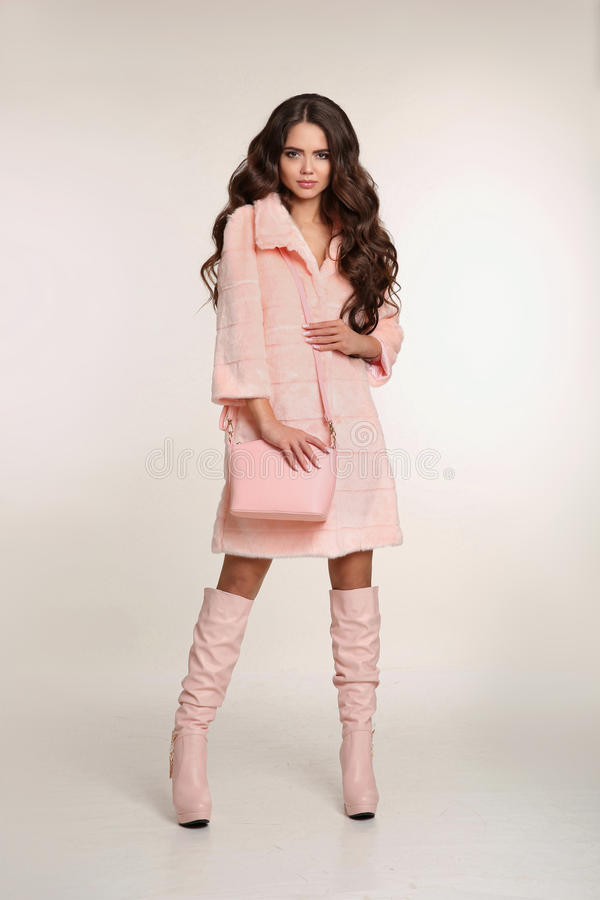 Fashion photo of fashionable woman in pink coat with handbag wears in trendy leather high boots posing isolated on studio stock photo