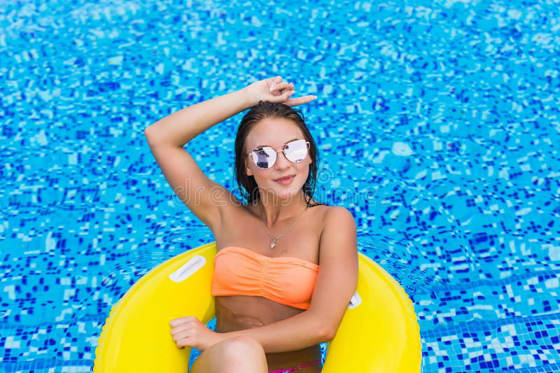Fashion photo of beautiful Girl in yellow top and sunglasses relaxing floating on inflatable ring. Outdoors lifestyle portrai stock photography