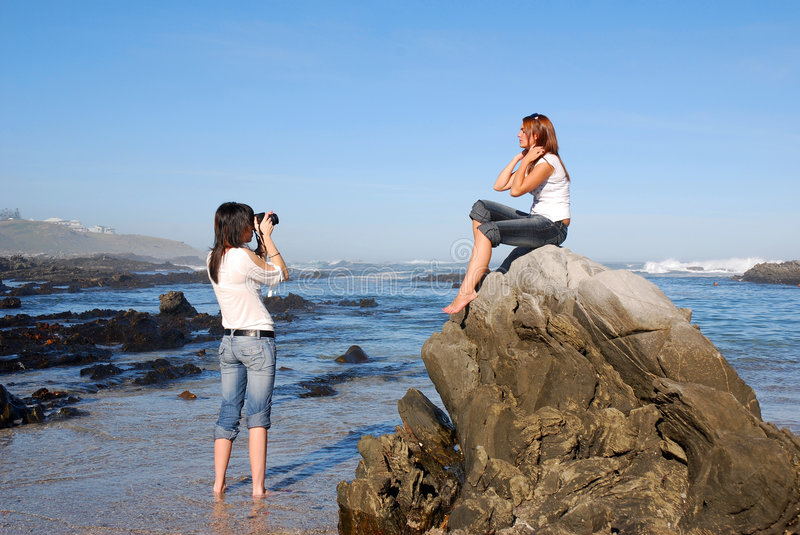 Fashion photo shoot. A female fashion photographer at work on a beach, taking pictures of a young caucasian casual dressed woman model sitting on the rocks next stock photography