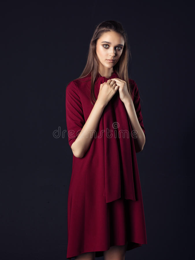 Fashion photo of young beautiful woman on black background. Fashion photo of young beautiful woman wearing red dress on black background royalty free stock photos