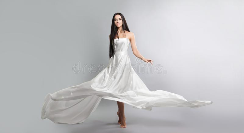 fashion photo of young girl in white dress flying tissue. Lightweight material. royalty free stock image