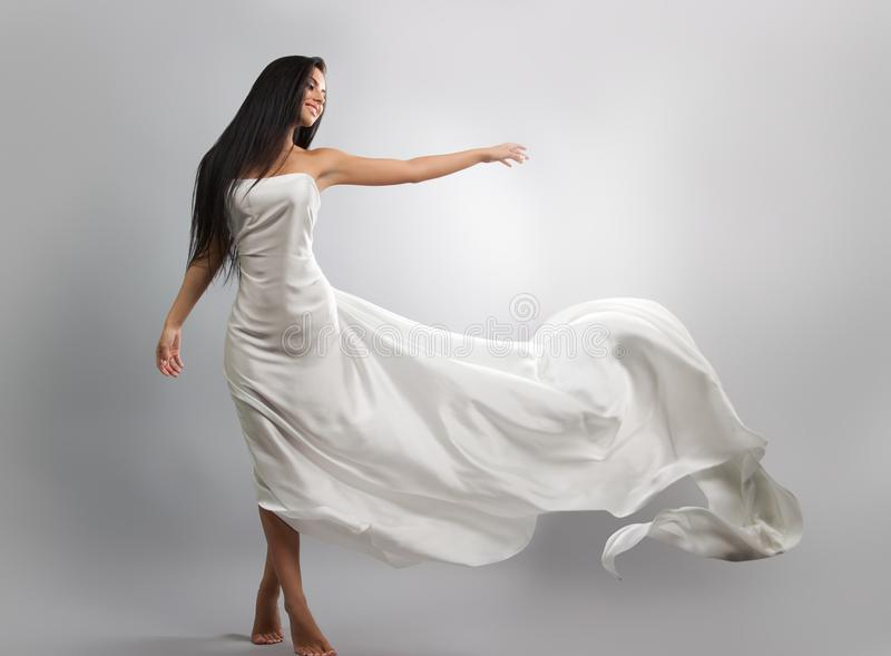 Fashion photo of young girl in white dress flying tissue. Lightweight material. stock image