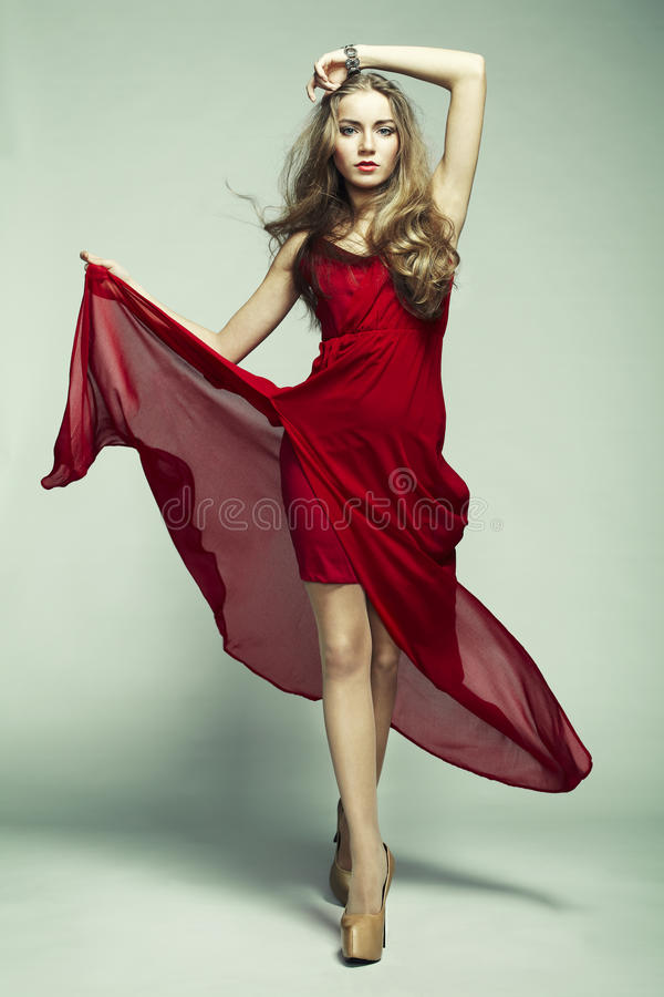 Fashion photo of young magnificent woman in red dress royalty free stock images