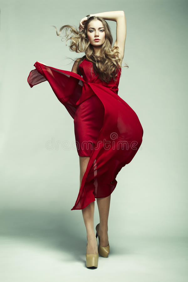 Fashion photo of young magnificent woman in red dress. Studio photo stock photo