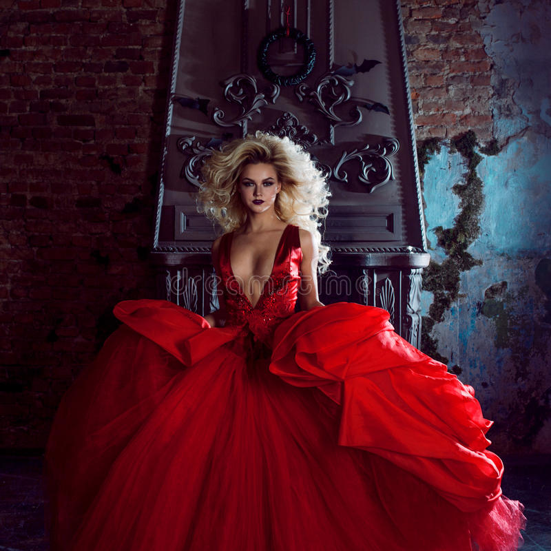 Fashion photo of young magnificent woman. Running towards camera. Seductive blonde in red dress with fluffy skirt royalty free stock images