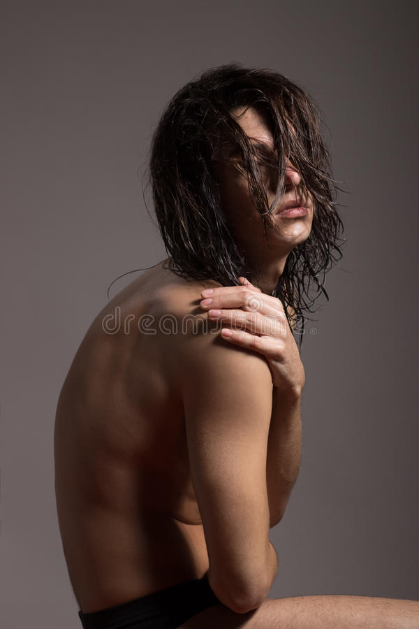 Fashion photography nude body young man model wet long hair. Studio stock images