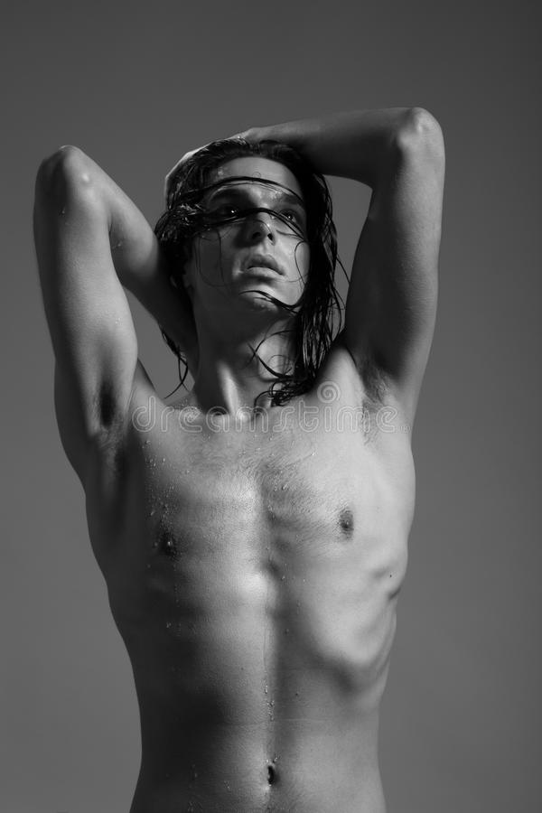 Fashion photography nude body young man model wet long hair. Studio royalty free stock photo