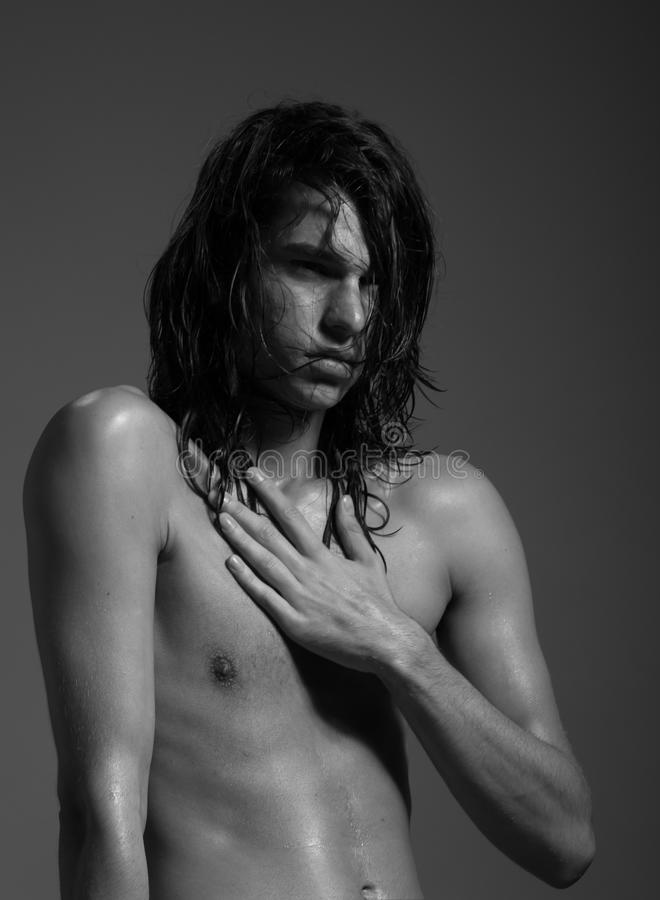 Fashion photography nude body young man model wet long hair. Studio royalty free stock photography
