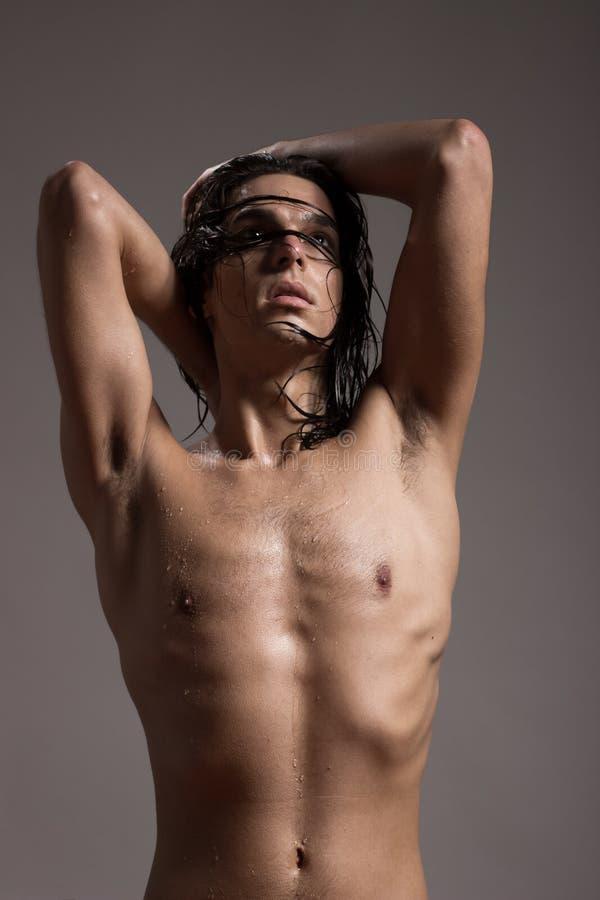 Fashion photography nude body young man model wet long hair. Studio stock photos