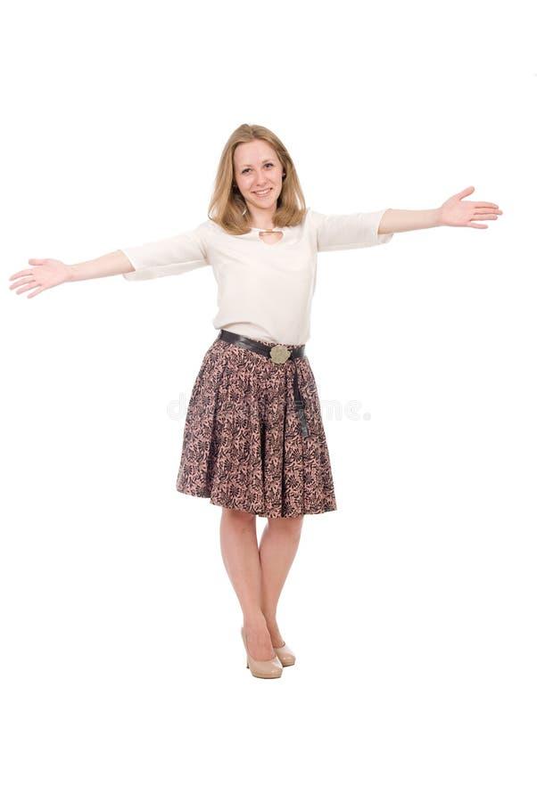 Fashion-porträtt av en ung blond i en kjol med vapen i motsatta riktningar i full tillväxt isolerad över arkivfoton