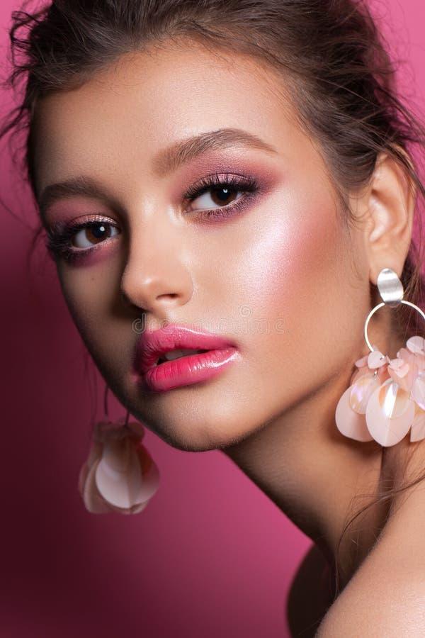 Fashion-porträtt av en vacker flicka med trendig rosa smink, tillbehör och bakgrund Brunettsmodell med hasselögon royaltyfri fotografi