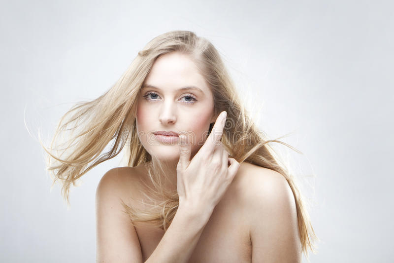 Fashion portrait. Of a beautiful blonde girl with hair fluttering in the wind stock photography