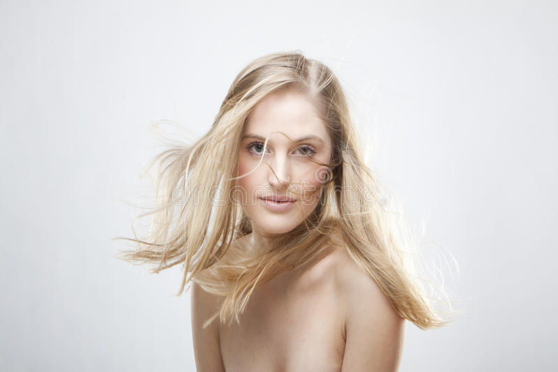 Fashion portrait. Of a beautiful blonde girl with hair fluttering in the wind royalty free stock photo