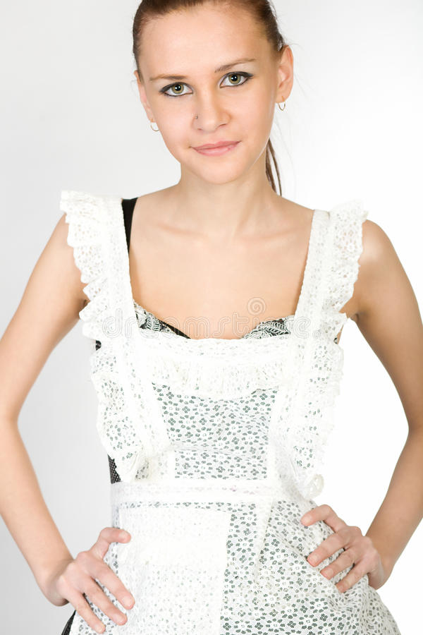 Fashion portrait. Young beautiful girl in a white school apron royalty free stock image
