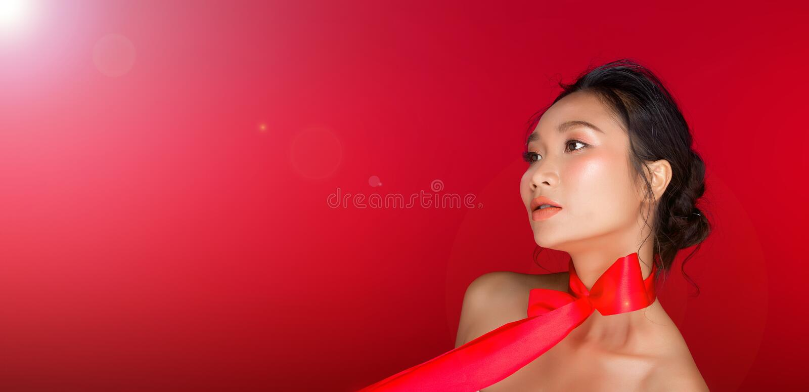 Asian tanned skin woman with strong color red lips. Fashion portrait of Asian Black hair tanned skin woman with strong color red lips, studio lighting red stock photo