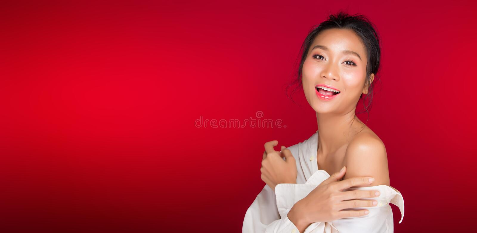 Asian tanned skin woman with strong color red lips. Fashion portrait of Asian Black hair tanned skin woman with strong color red lips, studio lighting red royalty free stock photo
