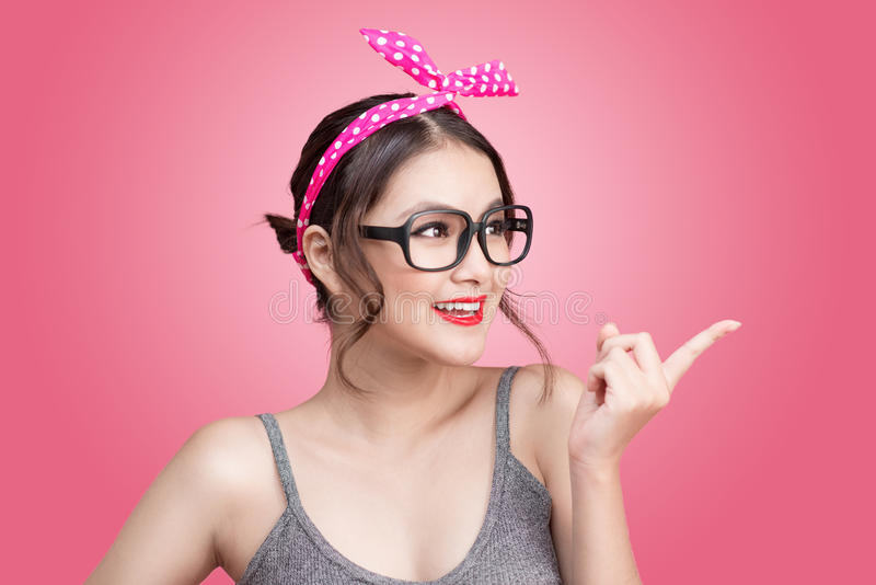 Fashion portrait of asian girl with sunglasses standing on pink royalty free stock photography