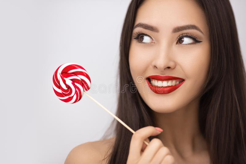 Fashion Portrait of Asian Woman with Lollipop in Studio royalty free stock images