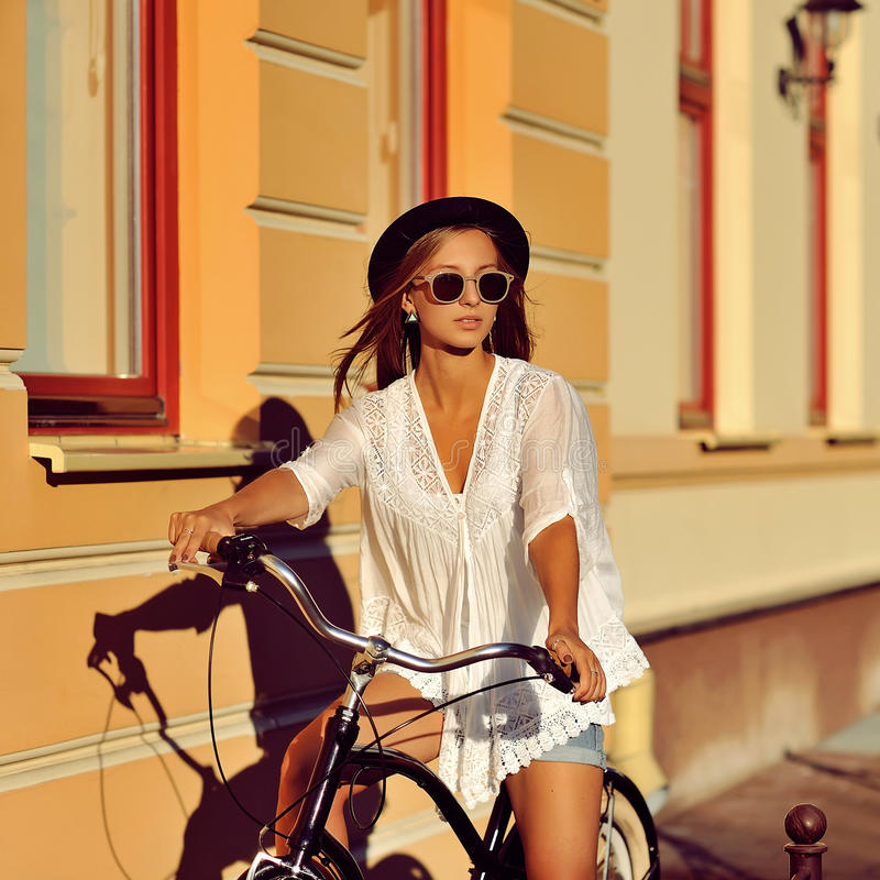 Fashion portrait of attractive blonde woman with a vintage bicycle outdoor stock photo