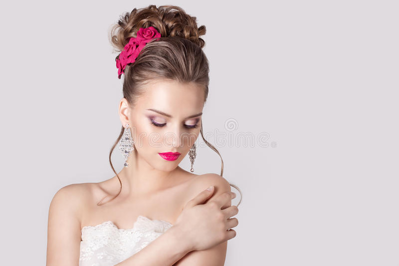 Fashion portrait of a beautiful attractive girl with a gentle elegant evening wedding hairstyles high and bright make-up with flow. Fashion portrait of a stock image